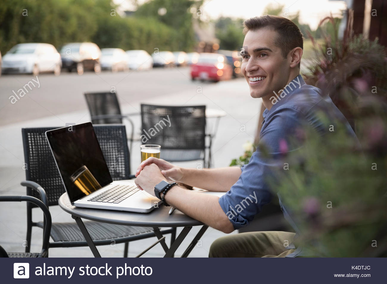 Smiling man drinking beer and using laptop at sidewalk cafe Photo Stock