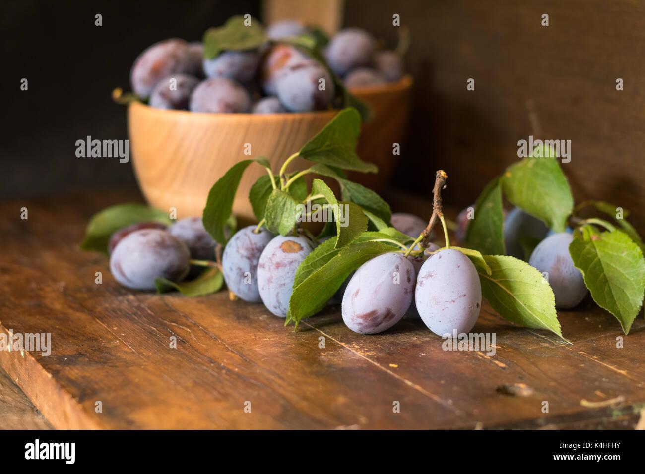 Prunes fraîches avec des feuilles vertes en pot en bois sur la table en bois sombre. faible profondeur de champ. Banque D'Images