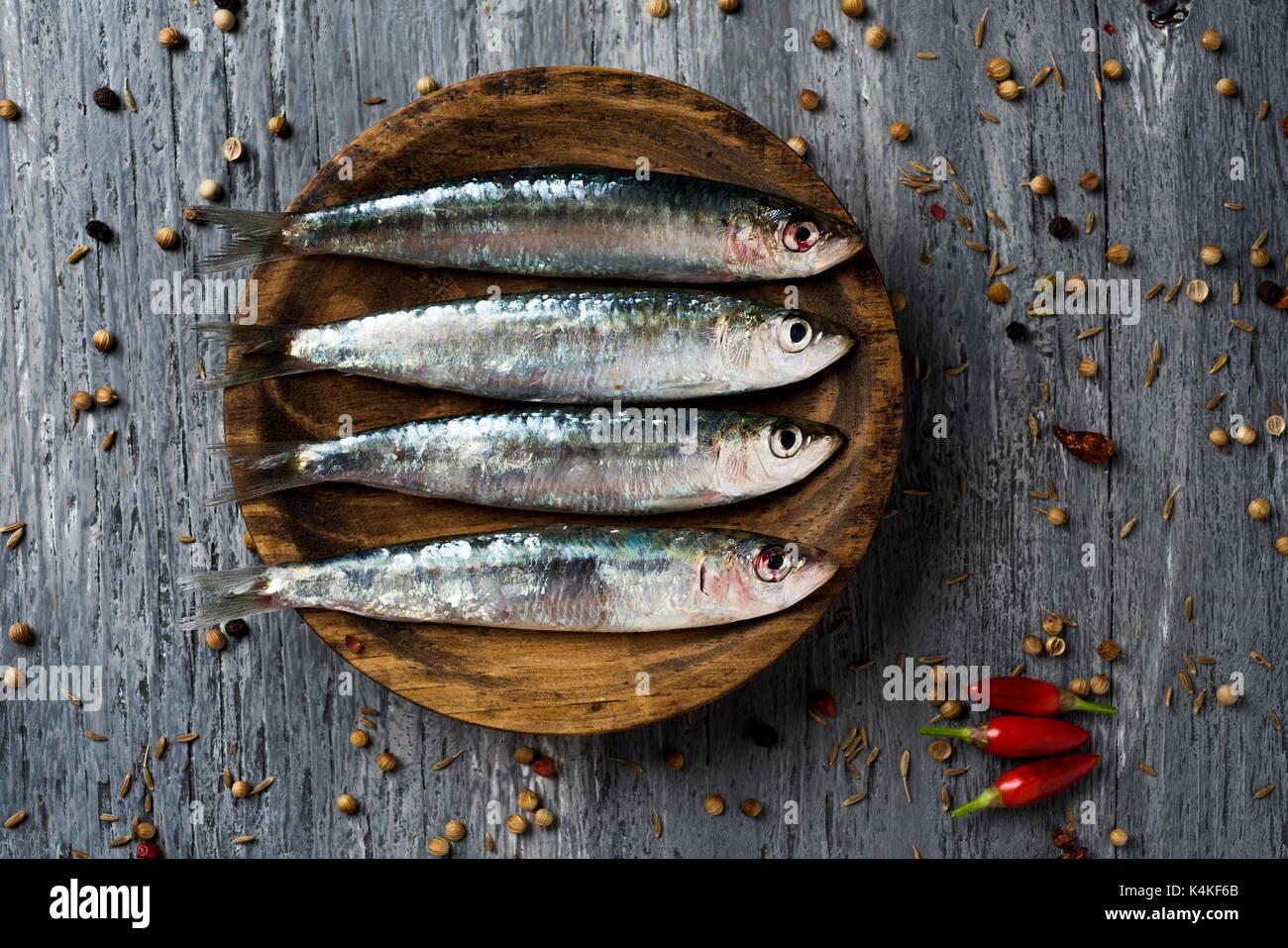 Tourné à angle élevé de certaines matières de sardines dans une plaque de bois, placé sur une table en bois rustique gris parsemé de grains de poivre Photo Stock