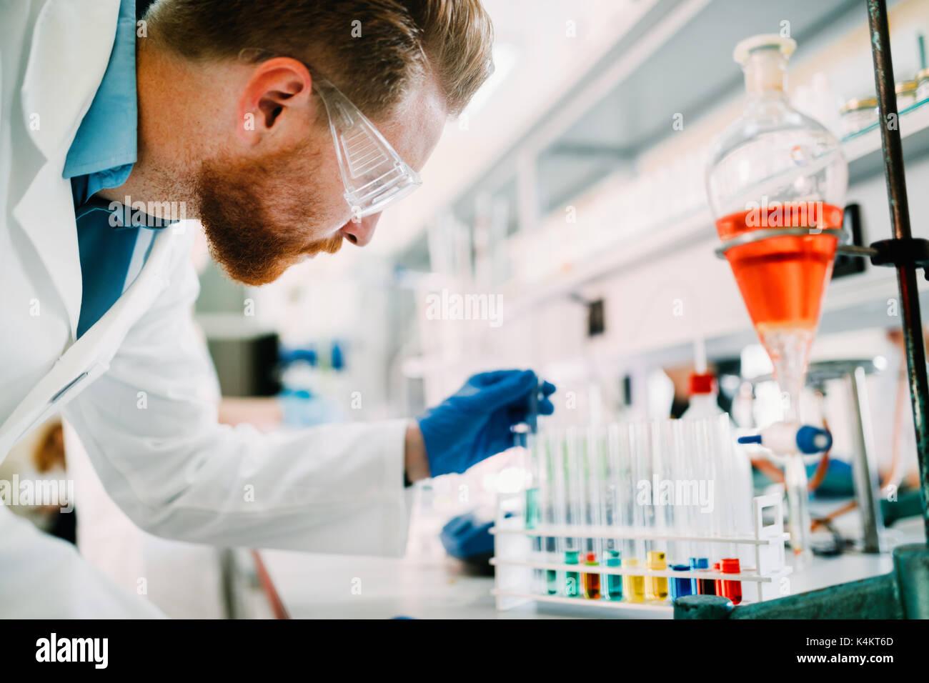 Beau étudiant en chimie working in laboratory Photo Stock