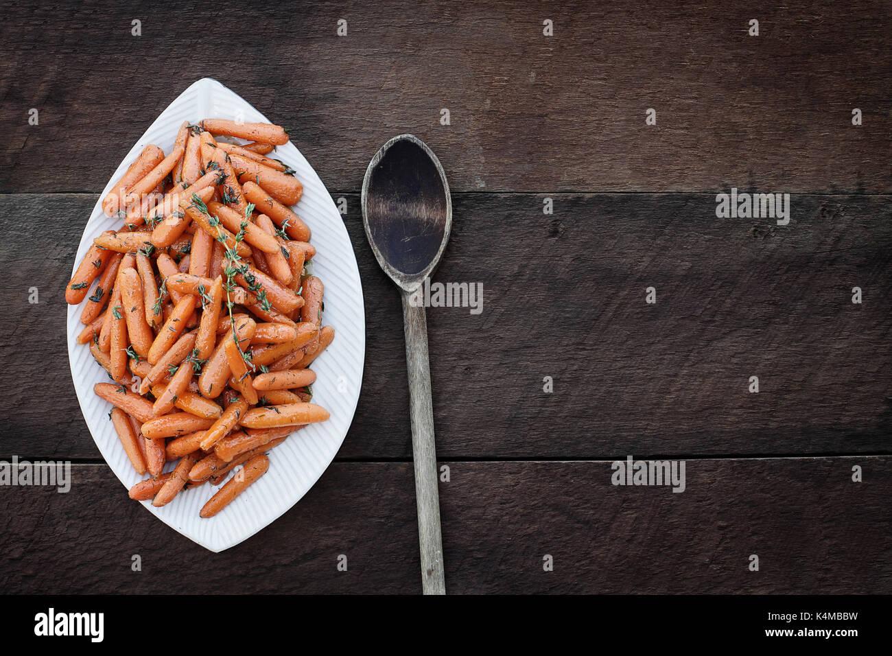 Jeunes carottes glacées au miel et vieille cuillère en bois. image en plongée des flatlay dans le style. Photo Stock