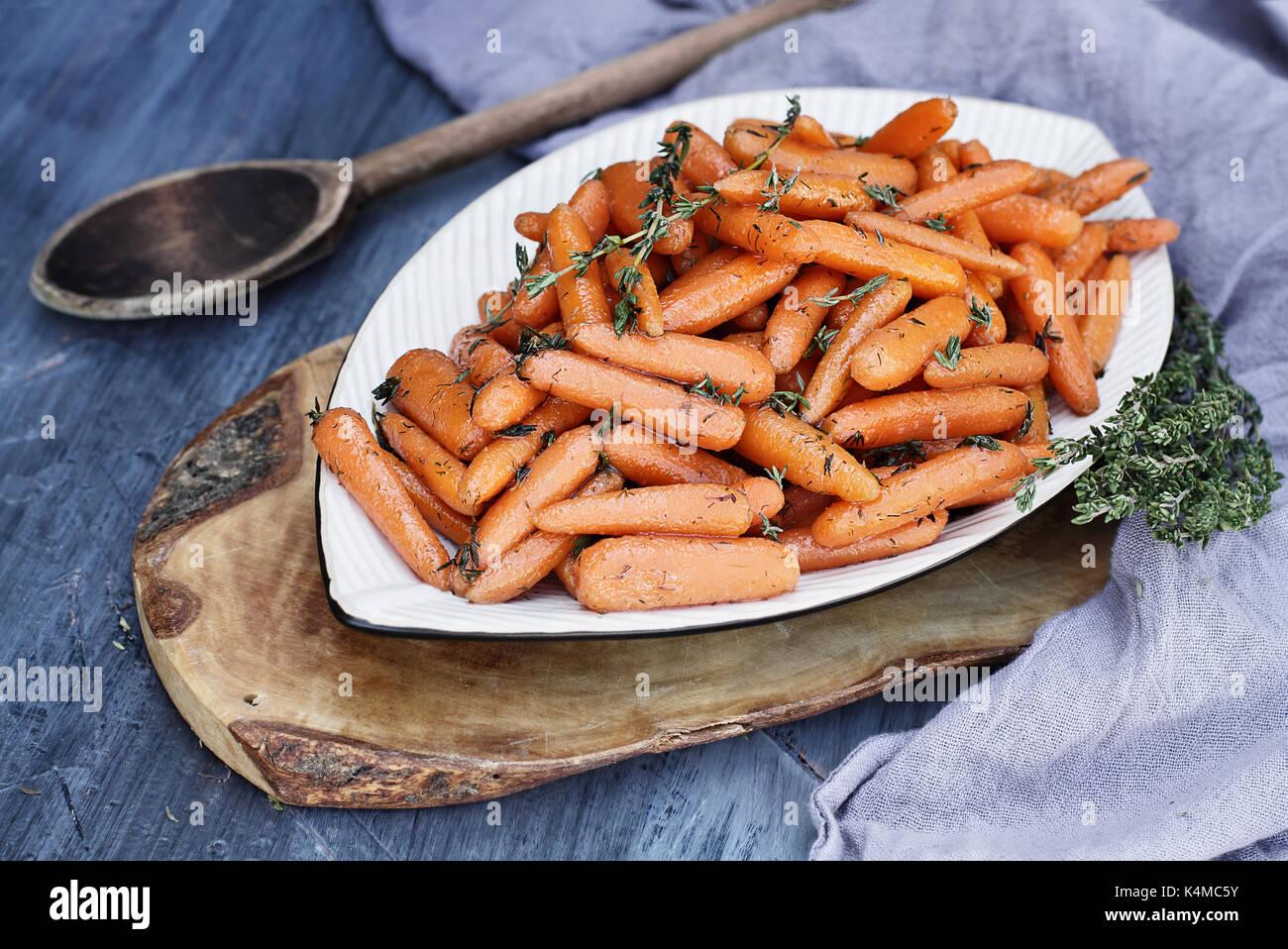 Jeunes carottes glacées au miel avec une vieille cuillère en bois rustique et le thym. L'extrême profondeur de champ avec l'accent sur les carottes en premier plan. Photo Stock