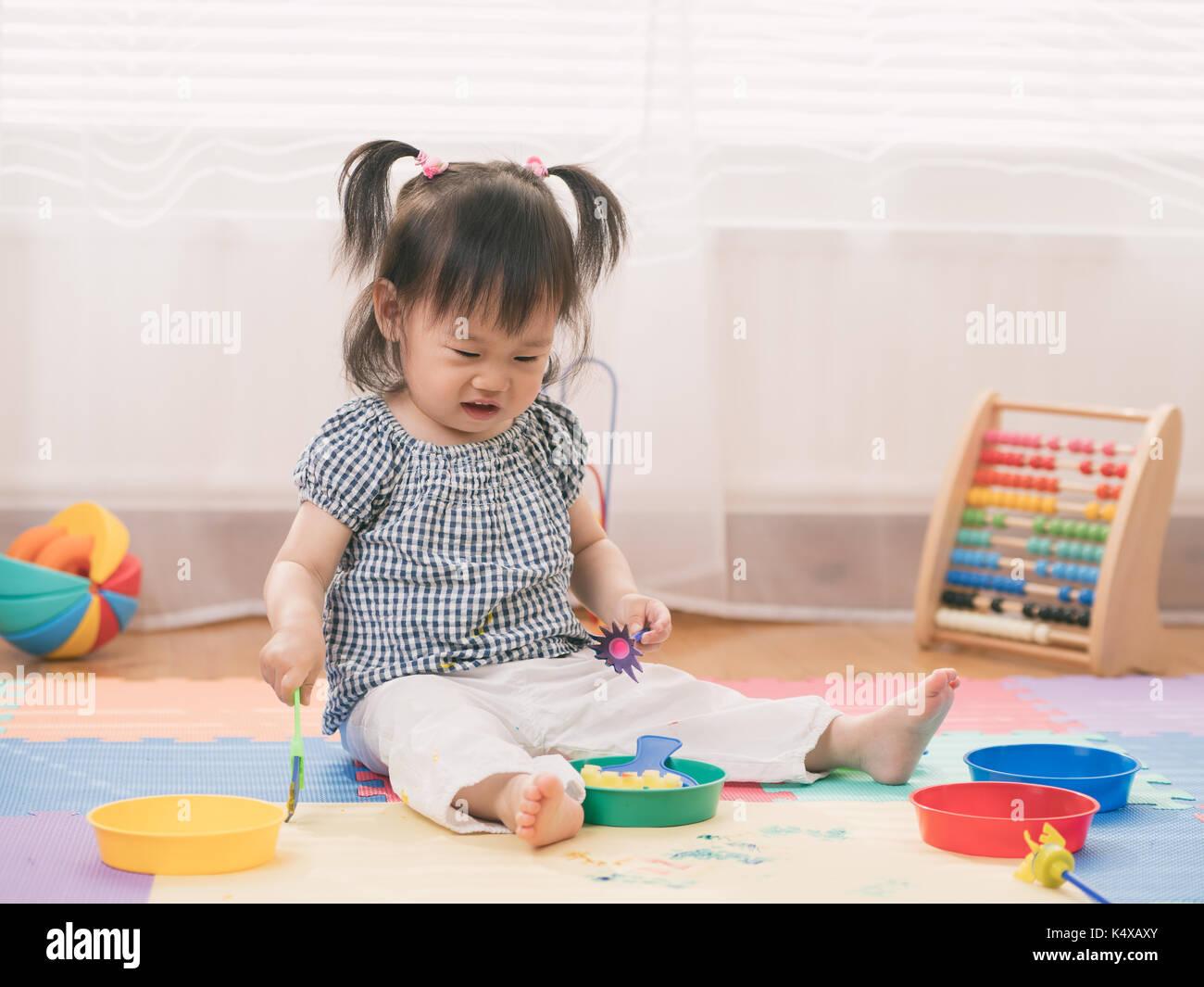 Baby Girl jouer les peintures au doigt à la maison Photo Stock