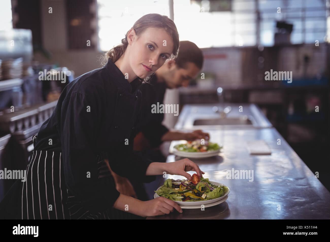 Portrait of smiling waitress preparing salad au compteur avec en chef de cuisine commerciale Photo Stock