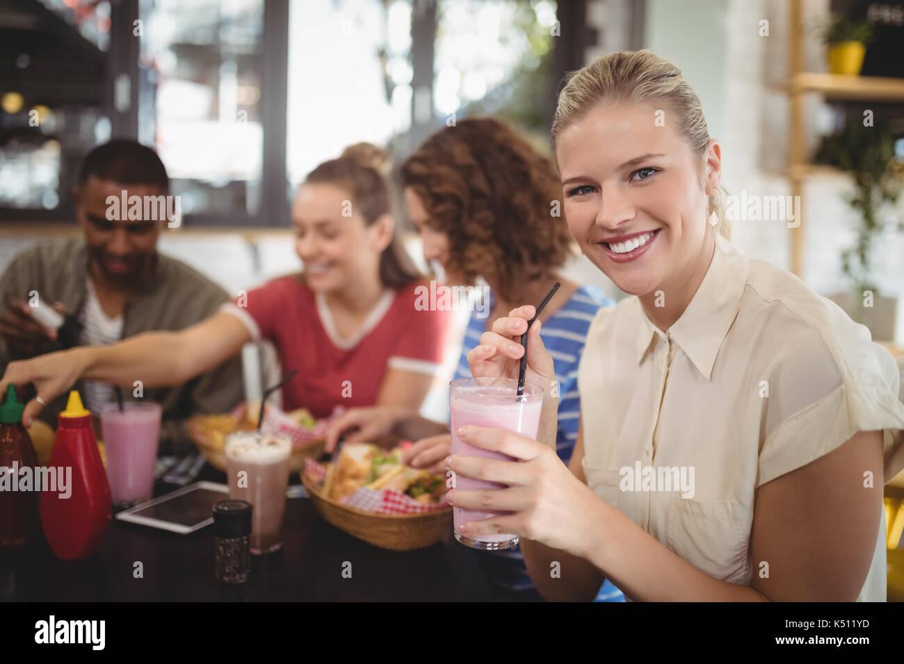 Portrait de jeune femme assis avec des amis lait frappé au café Banque D'Images