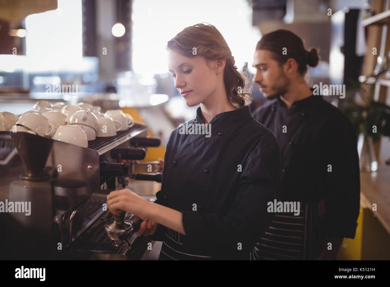 Les jeunes à l'aide du personnel d'attente machine à expresso debout dans coffee shop Photo Stock