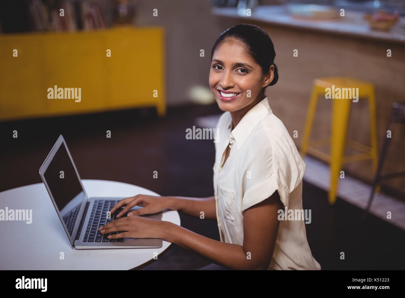 Side view portrait of smiling young woman using laptop in coffee shop Photo Stock