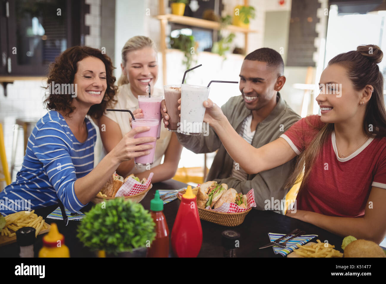 Happy friends raising boissons tout en sitting at table in coffee shop Banque D'Images