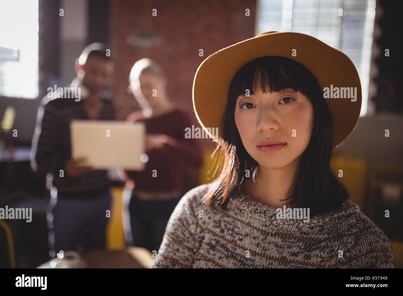 Portrait of young woman wearing hat debout contre des collègues in coffee shop Photo Stock