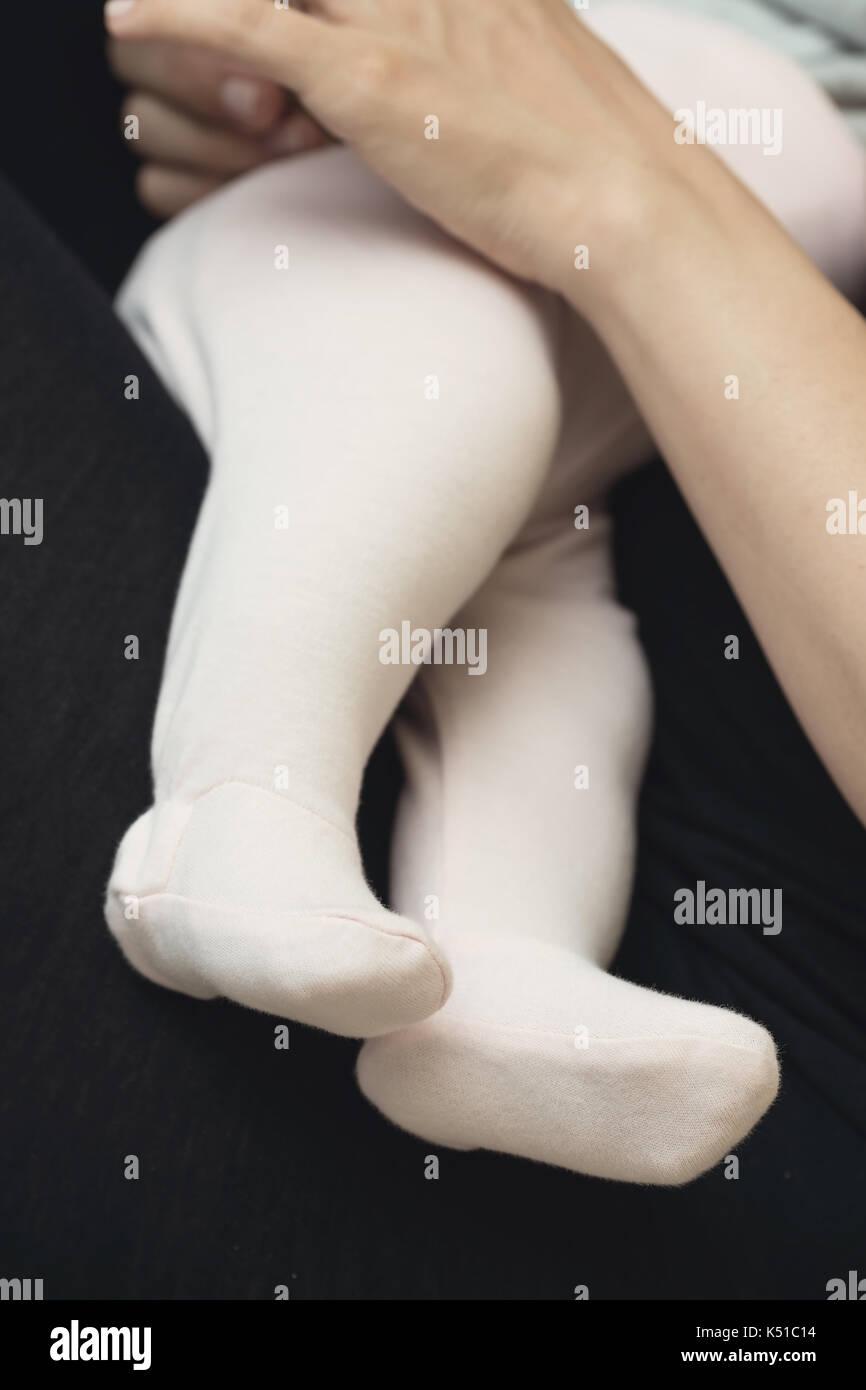 Les jambes du bébé habillé en petit bas sur les genoux de sa mère pendant l'allaitement, mother's hand holding le bébé nouveau-né Banque D'Images