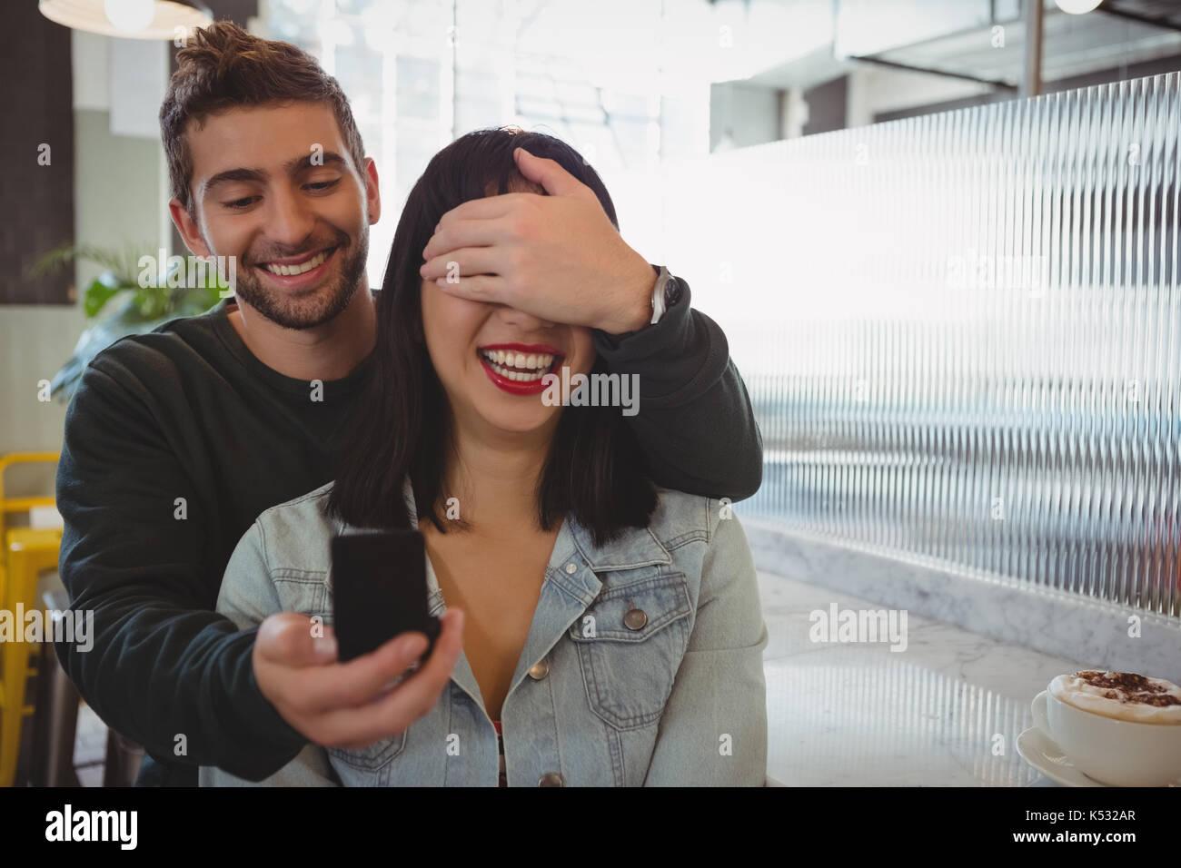 Jeune homme couvrant les yeux tandis que la petite amie à l'anneau de don cafe Banque D'Images