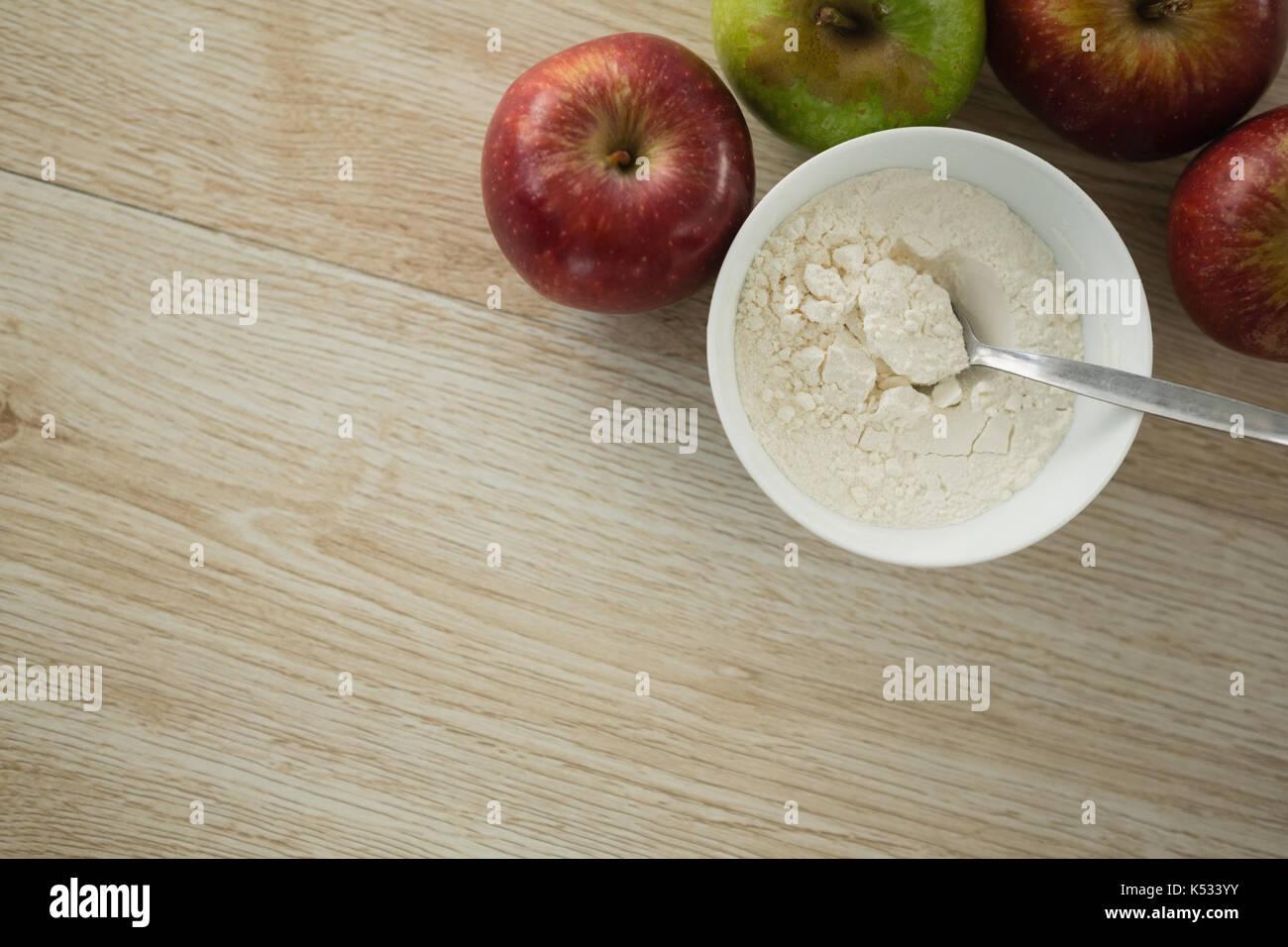 Tourné directement au-dessus de la farine dans un bol de pommes sur table en bois Photo Stock