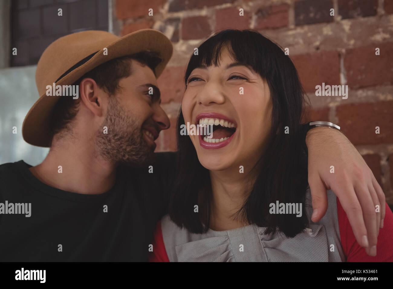 Jeune homme chuchotant à l'oreille cheerful woman at cafe Photo Stock