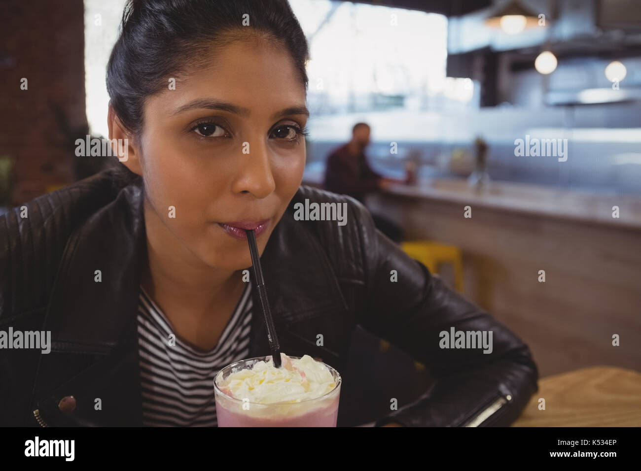 Portrait of young woman drinking milk-shake au café Banque D'Images