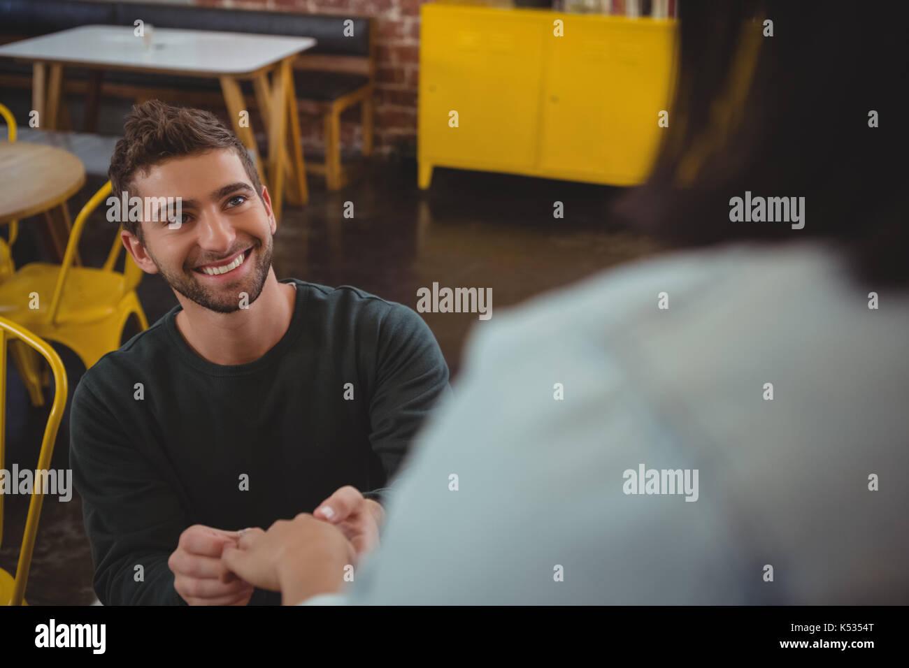 Smiling young man holding amie part au café Photo Stock