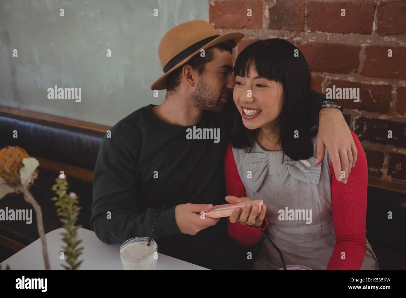 Jeune homme chuchotant à l'oreille femme assis à cafe Photo Stock