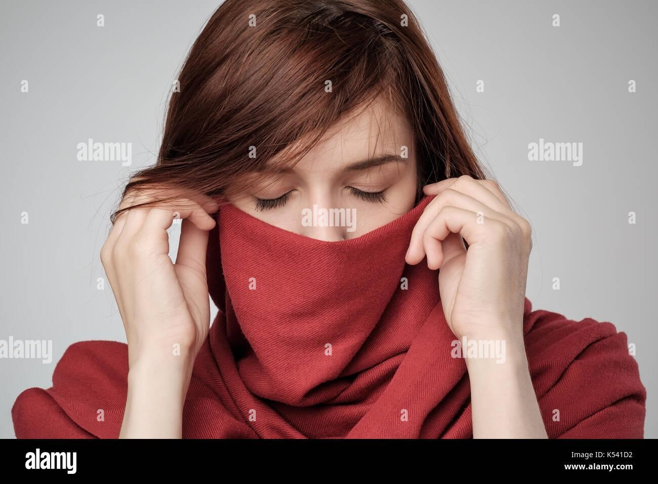 Portrait de femme aux cheveux rouge se cachant le visage avec écharpe. 96527c5ab26