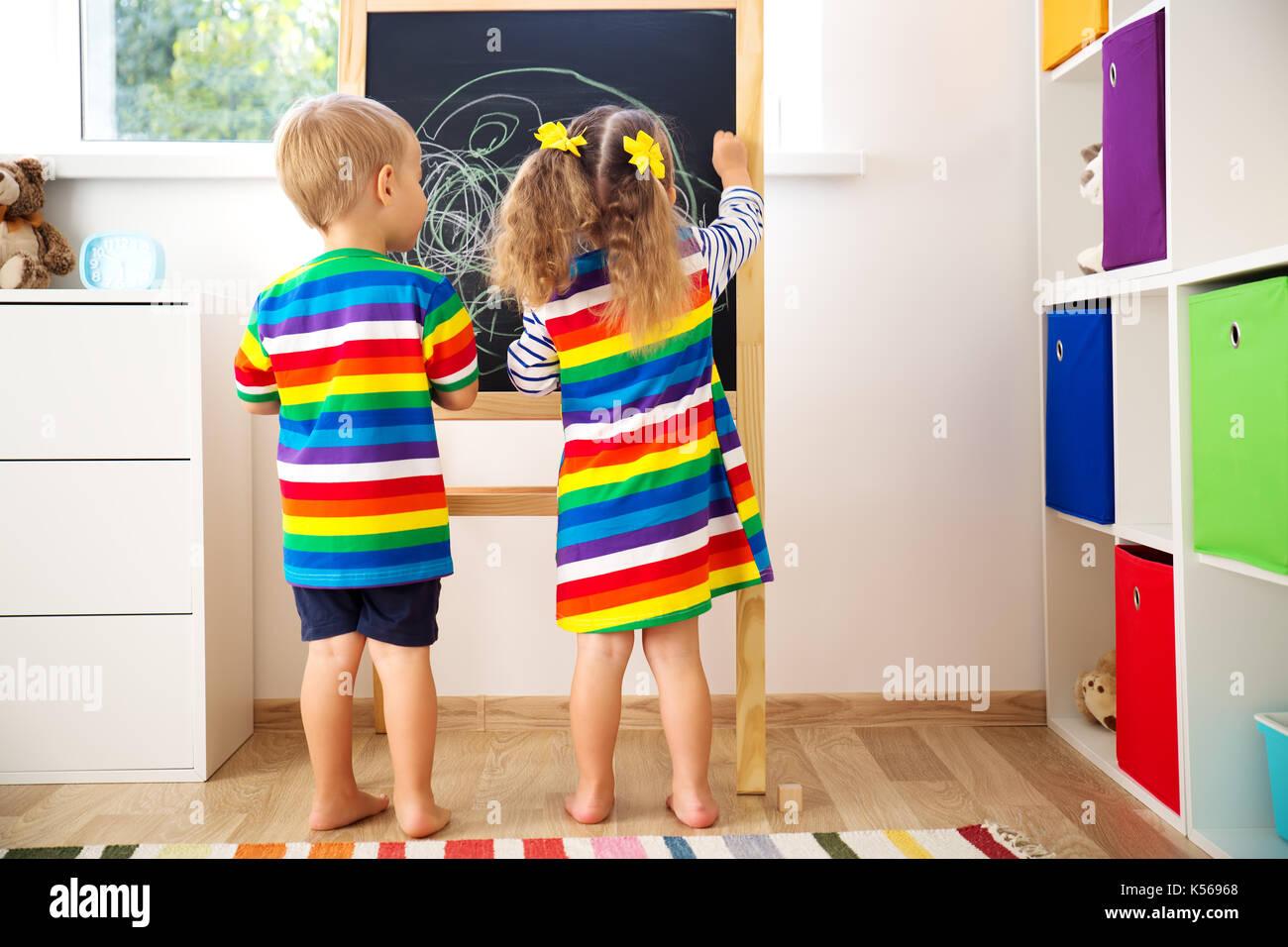 Petit enfant dessin sur le tableau noir Photo Stock