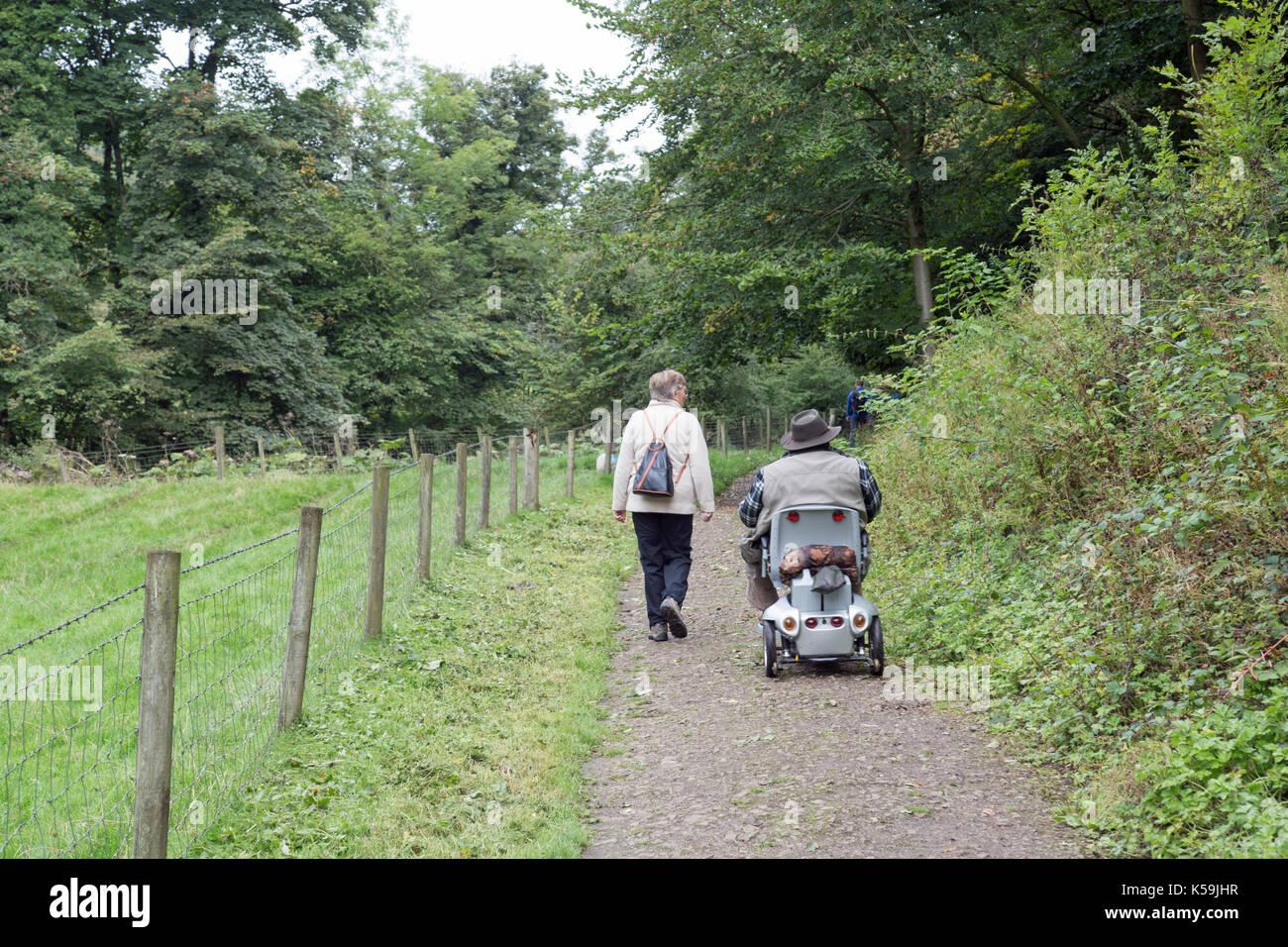 Septembre 2017, un couple, une mobilité et en utilisant une aide à la mobilité voyager sur un chemin dans la campagne. Photo Stock