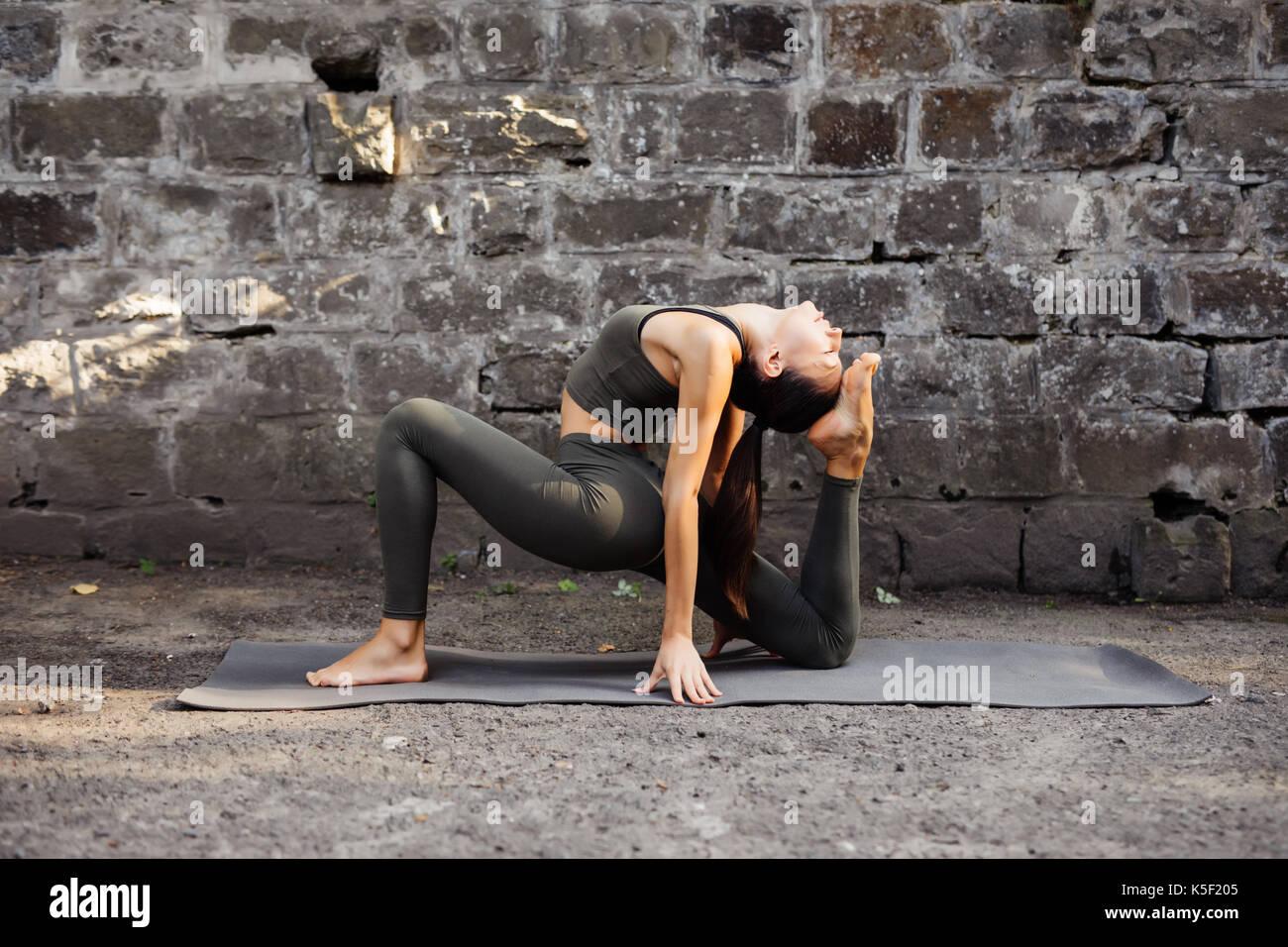 Woman practicing yoga contre un mur de briques Photo Stock