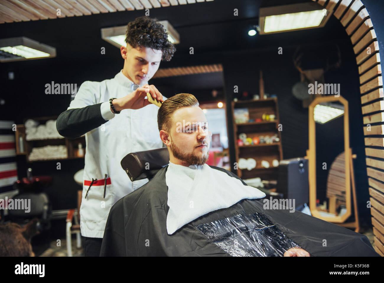 Le salon de coiffure homme en train de couper la barbe de tondeuse électrique client Photo Stock