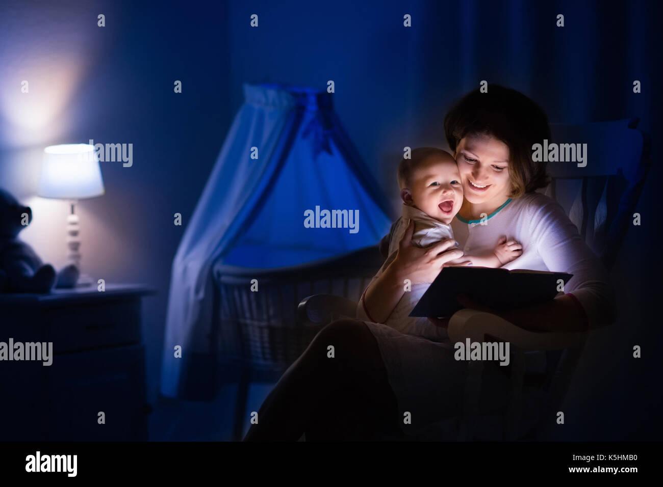 la mère et l'enfant de lire un livre dans une chambre sombre. maman