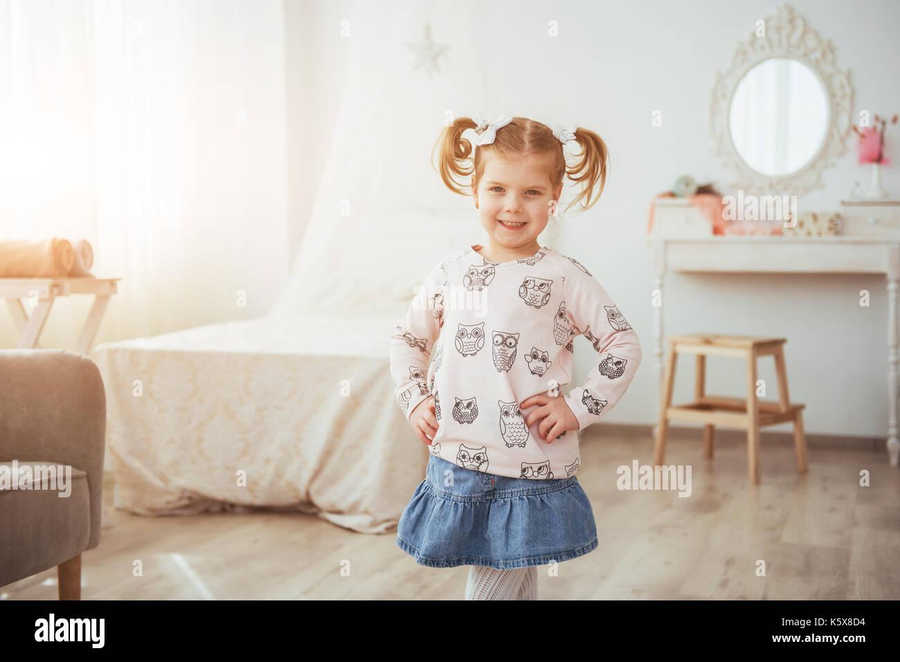 Heureux visage drôle de fille de bébé dans une salle lumineuse. Photo Stock