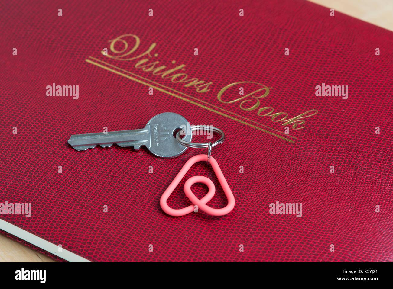 Un porte-clés avec le logo Airbnb Belo repose sur un livre des hôtes dans un appartement à louer. Photo Stock