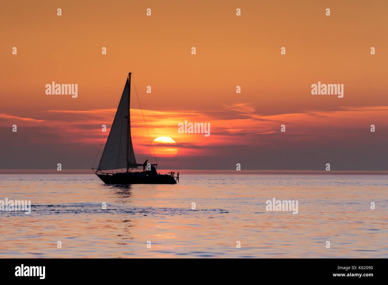 Une personne de mettre les voiles sur un bateau au coucher du soleil sur l'horizon de la baie de Cardigan Photo Stock