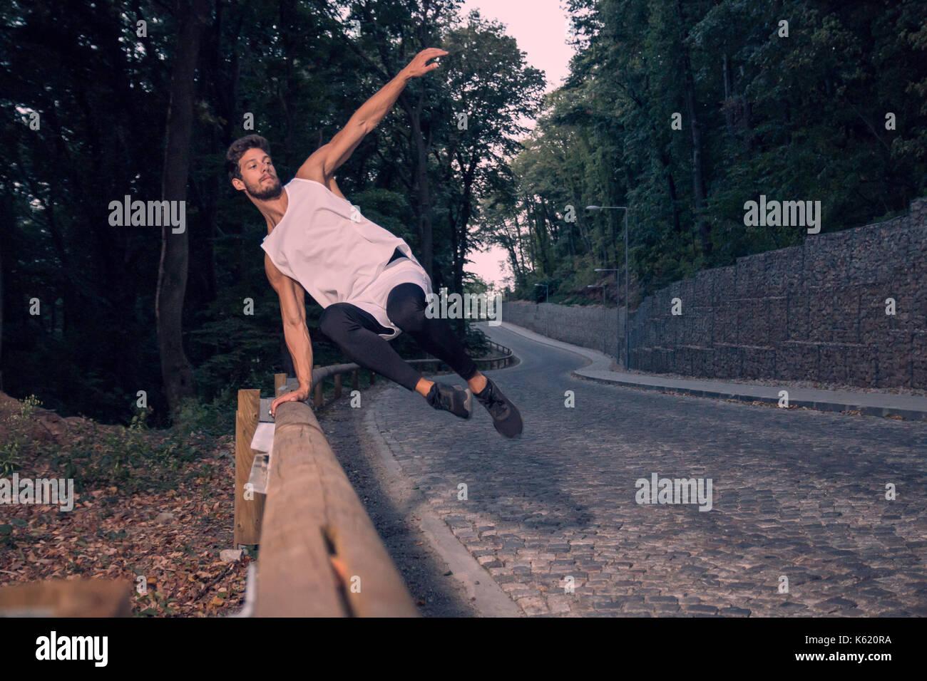 Deux jeunes gens, l'aventure, à l'extérieur, forêt route man jumping fence, parkour street stunt, région rurale, le saut dans l'air Photo Stock
