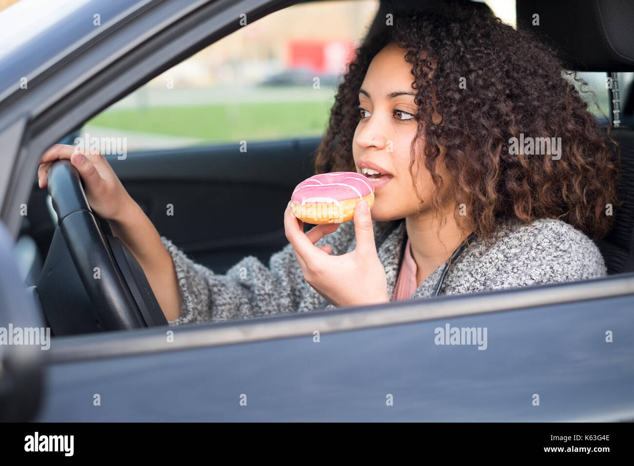 Woman eating a sweet conduisant sa voiture Photo Stock