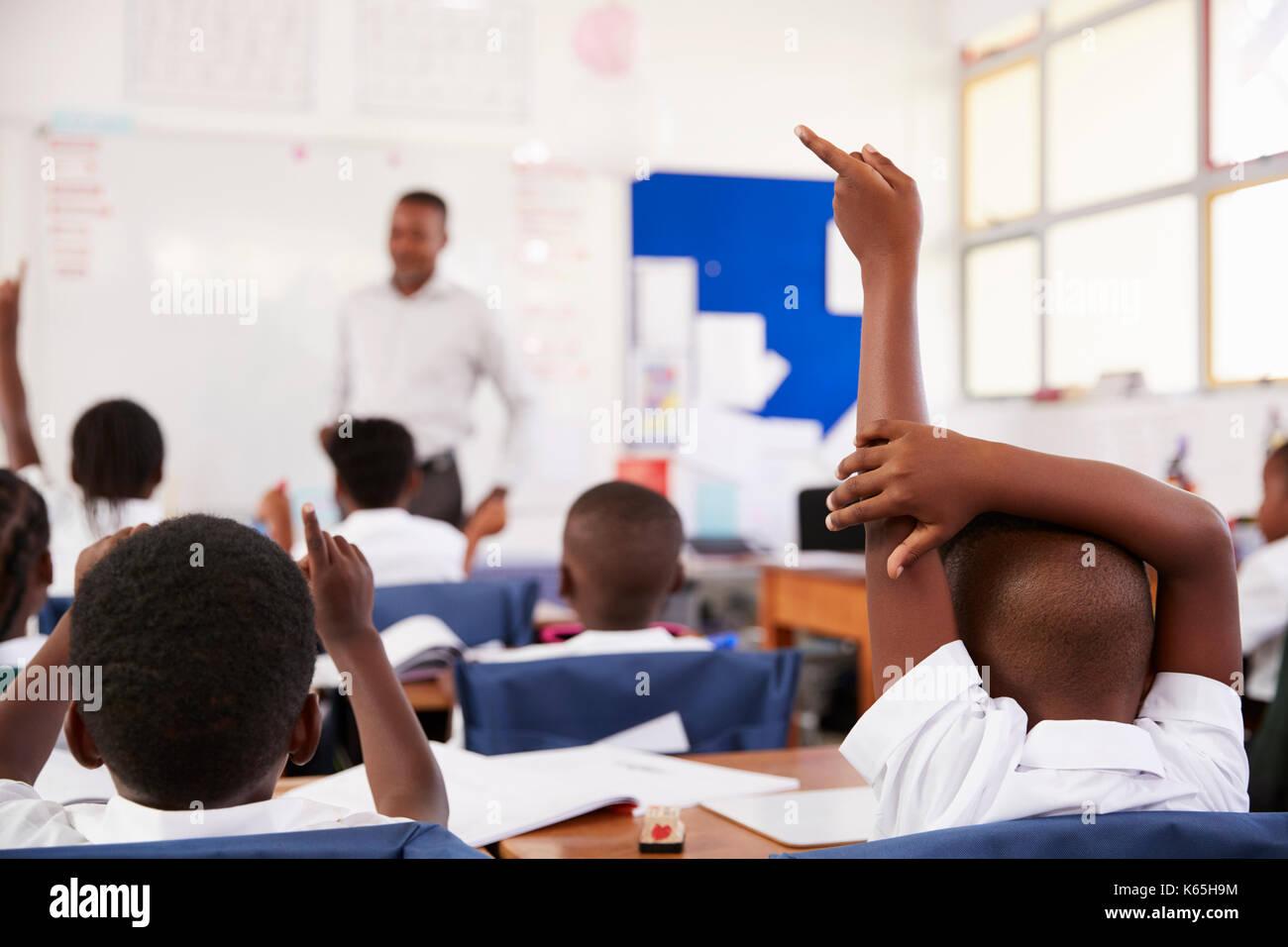 Des mains des enfants pour répondre à l'enseignant dans une école élémentaire leçon Photo Stock
