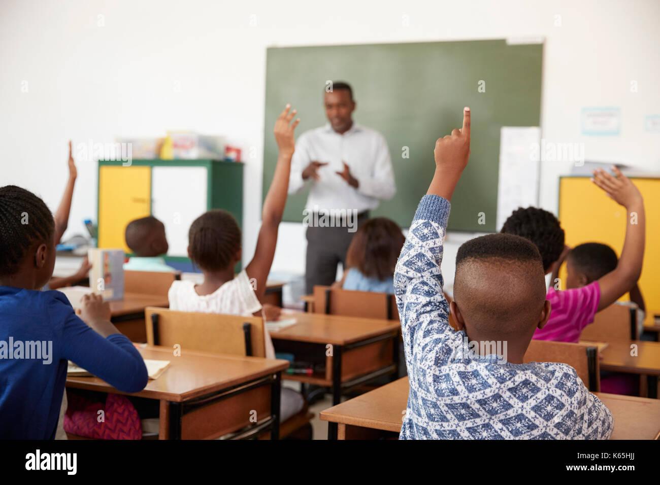 Les enfants sensibilisation mains pendant une leçon à l'école élémentaire Photo Stock