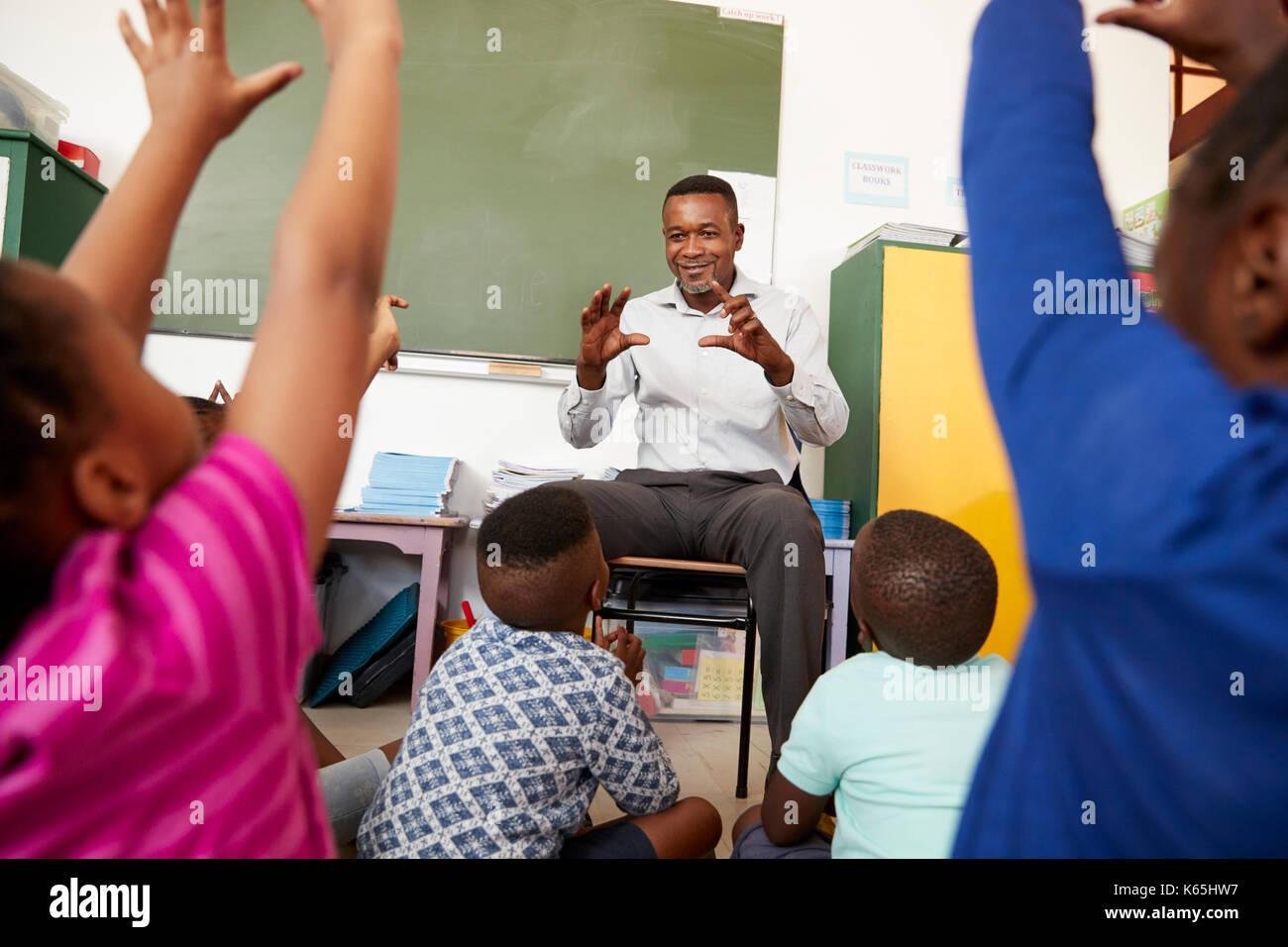 Les enfants de l'école élémentaire à l'écoute de l'enseignant Photo Stock