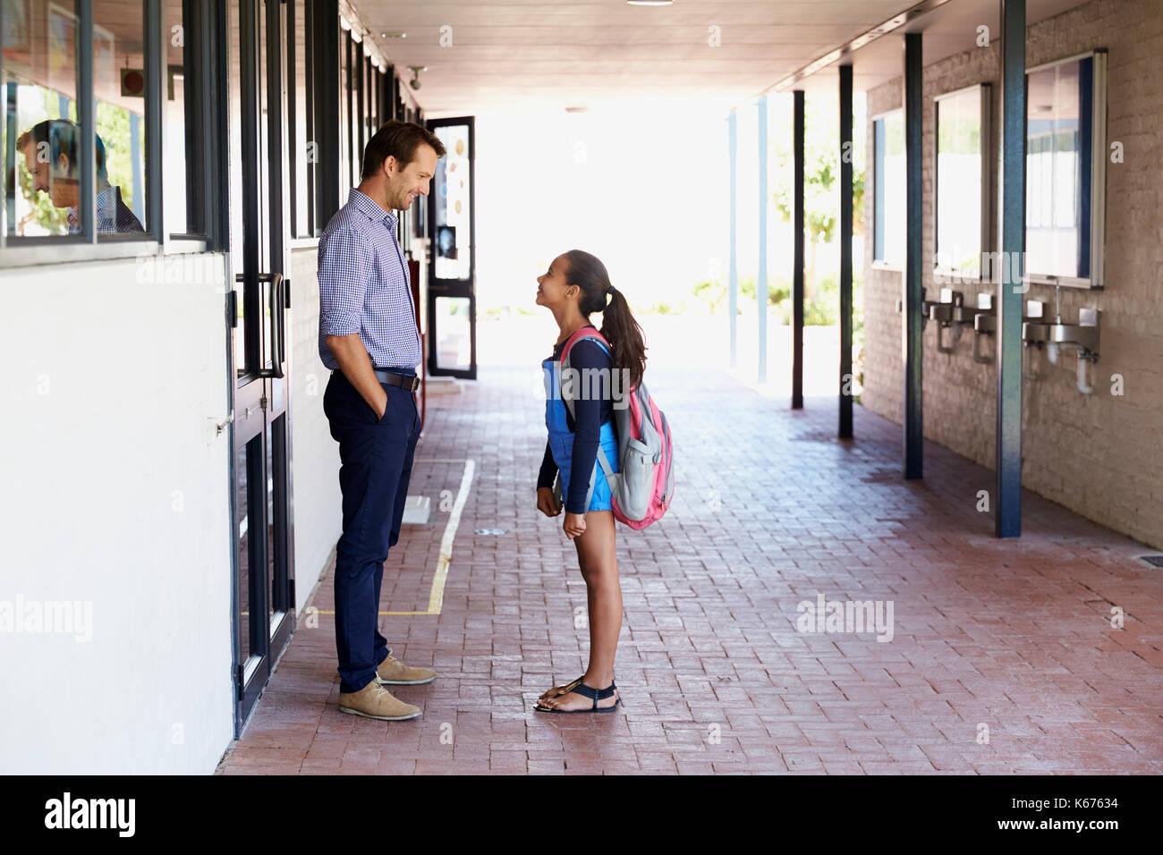Parler avec l'enseignant de l'école en dehors de la classe d'écolière Photo Stock