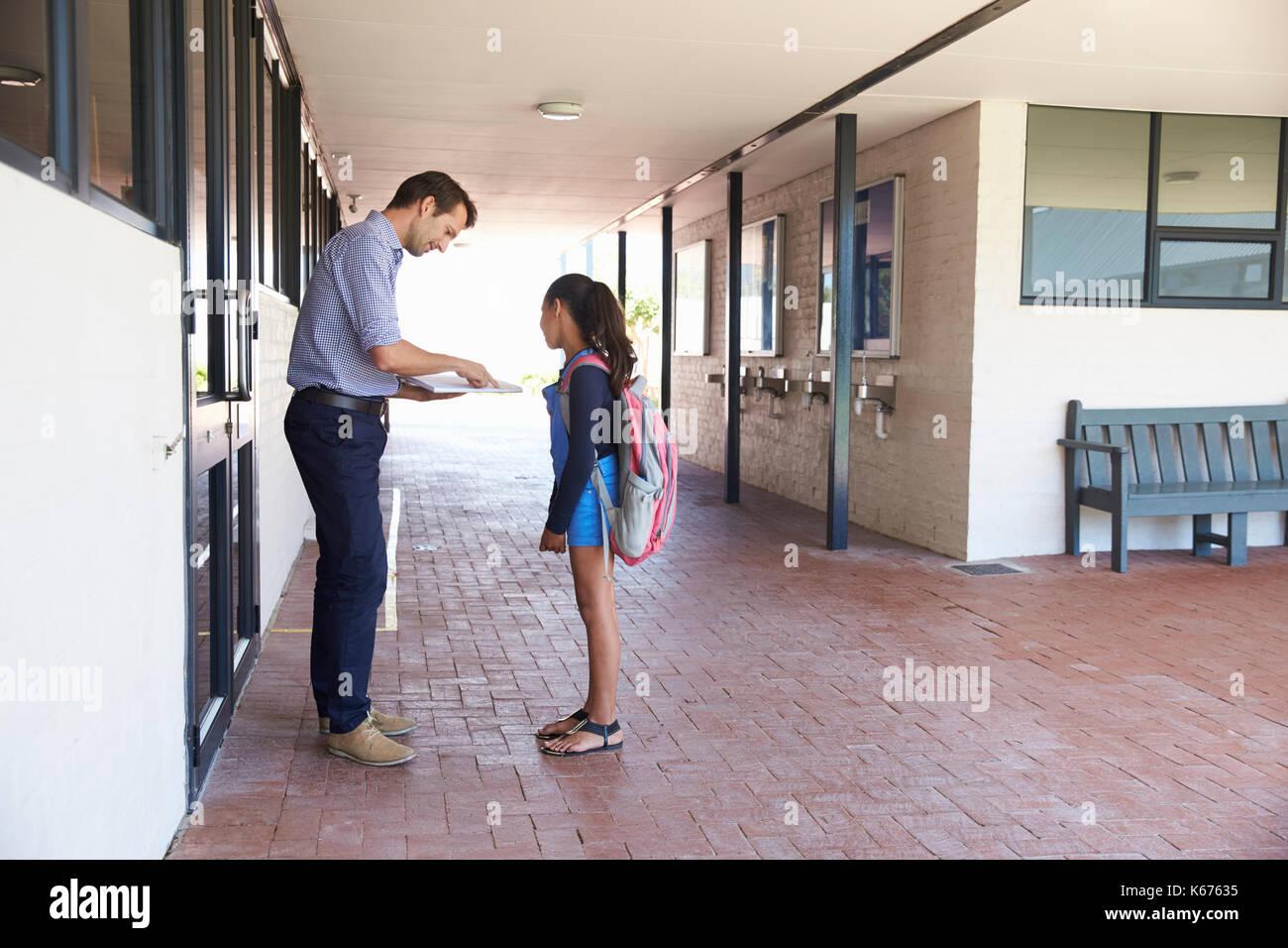 Enseignant de l'école montrant livre à lycéenne en dehors de la classe Photo Stock