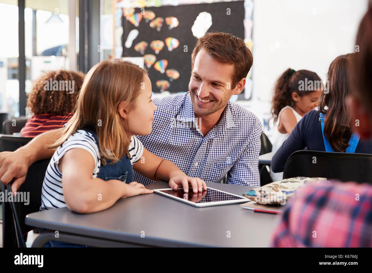 L'enseignant et à l'aide d'écolière de tablette Photo Stock