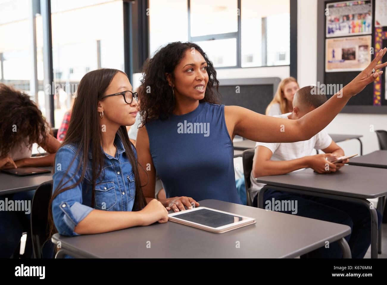 Enseignant travaillant avec les points d'écolière au conseil Photo Stock
