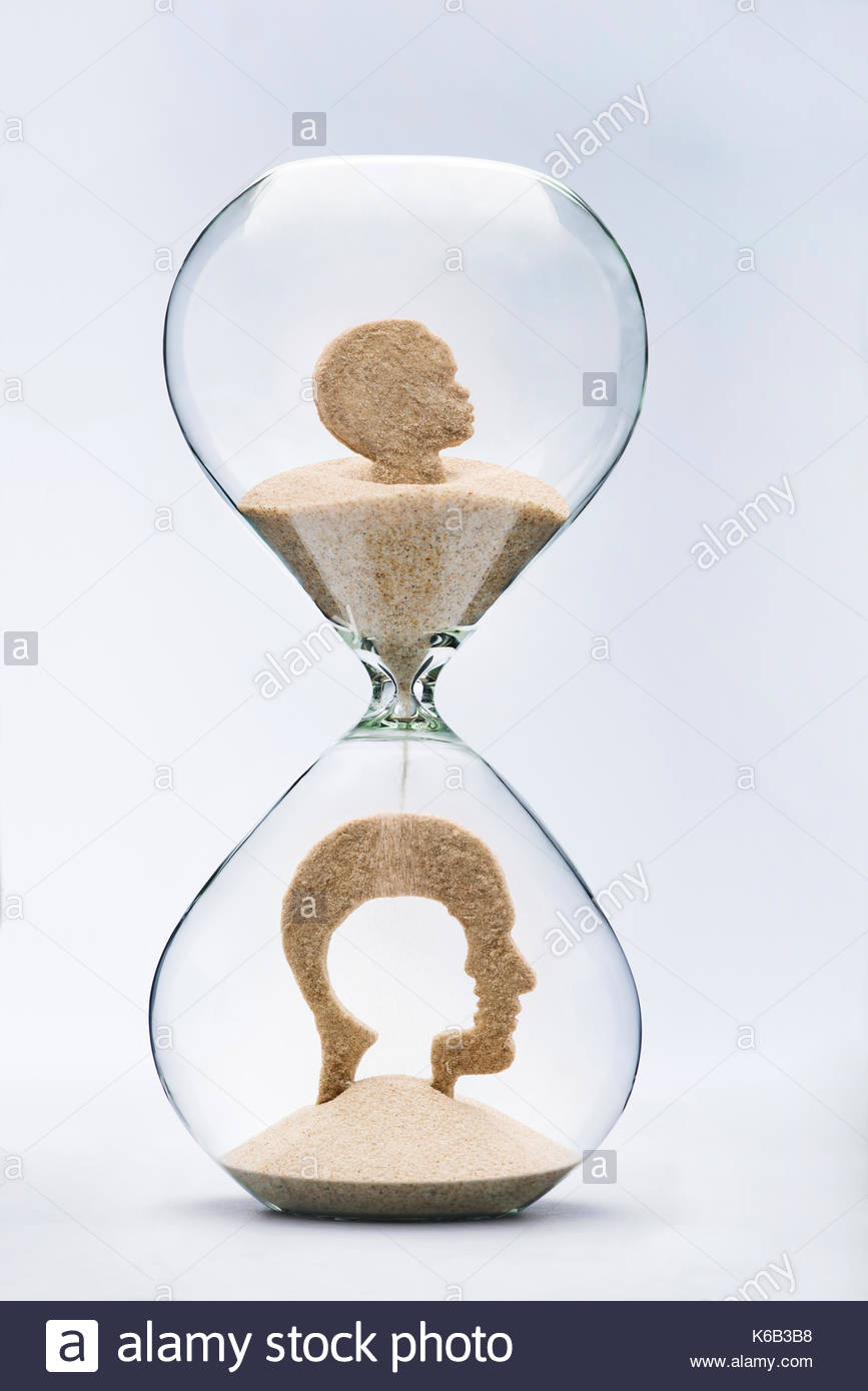 Nostalgie de la petite enfance concept avec sable chute en prenant la forme d'une coupe de la tête à l'intérieur d'une tête d'homme, à l'intérieur d'un sablier Photo Stock