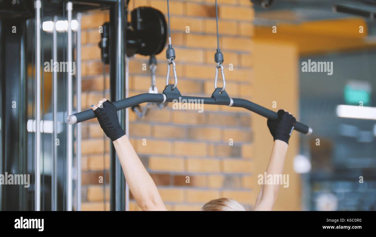 Club de remise en forme - femme effectue des exercices pour les mains dans la salle de sport Photo Stock