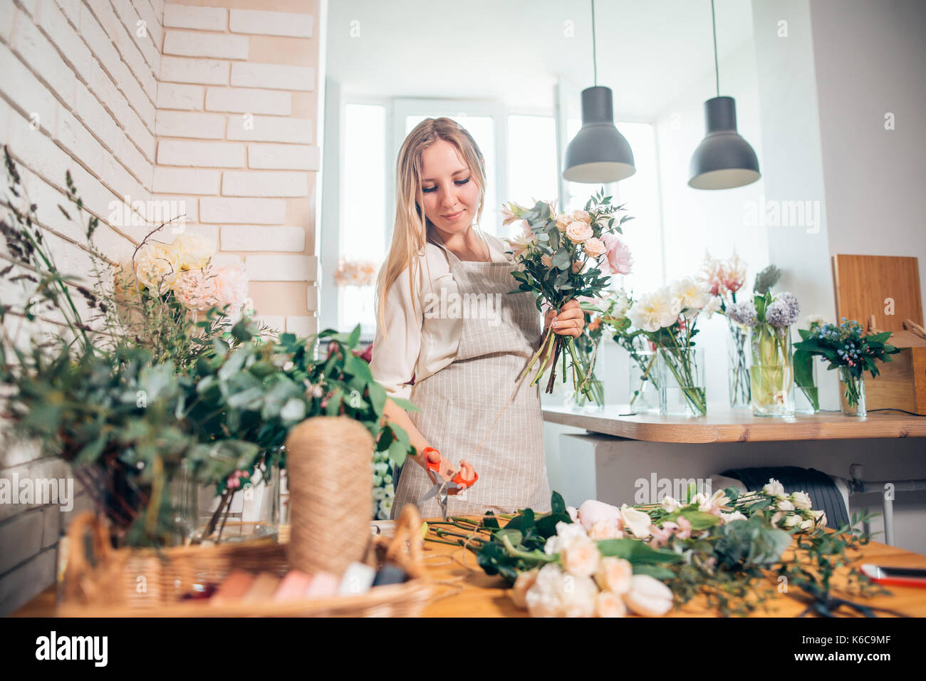 Lieu de travail: organisation de femme fleuriste un bouquet de roses, fleurs, Ranunculus matthiolas et Gypsophila paniculata brindilles. Photo Stock