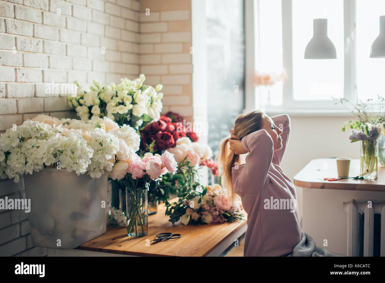 Heureux belle jeune femme fleuriste à lunettes assis dans le magasin de fleurs Photo Stock
