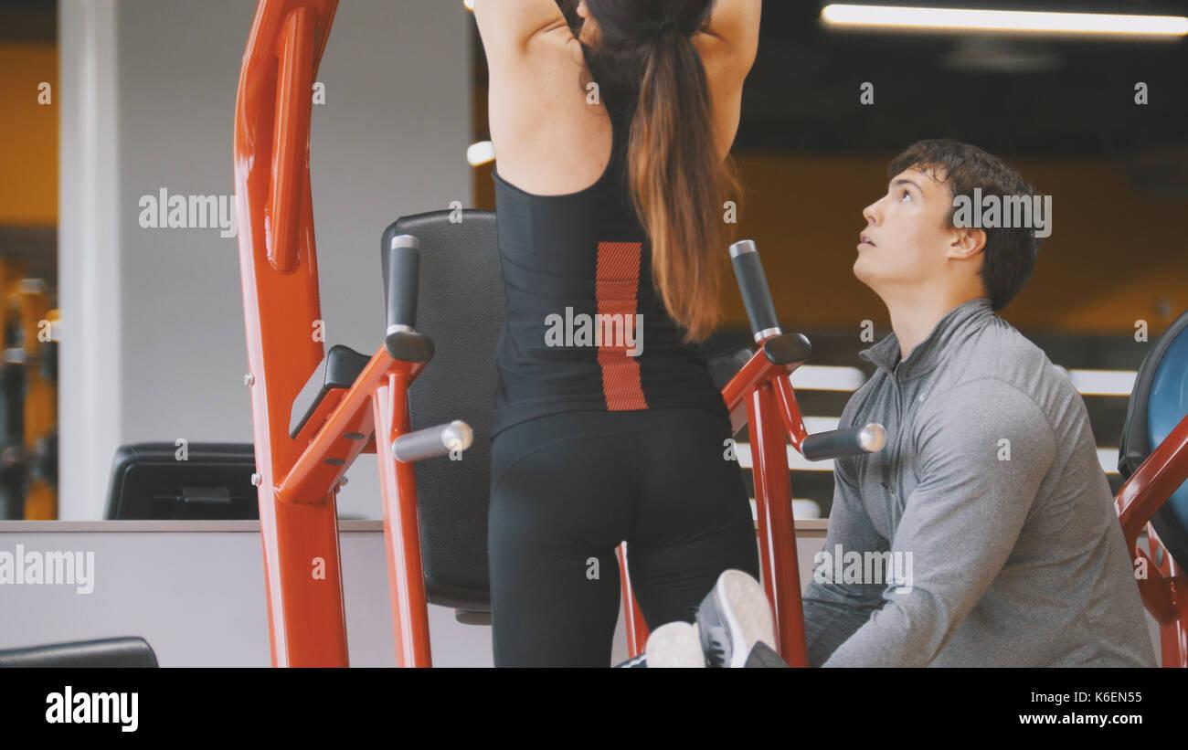Fitness-club - jeune femme effectue tirer-se lève avec entraîneur masculin - Vue arrière, Close up Photo Stock