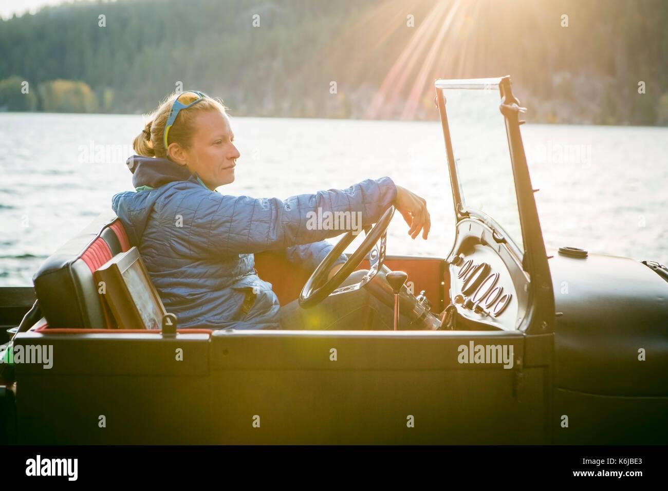 Jeune femme assise Vue de côté en camion rénové en regardant le coucher du soleil, New York, USA Banque D'Images