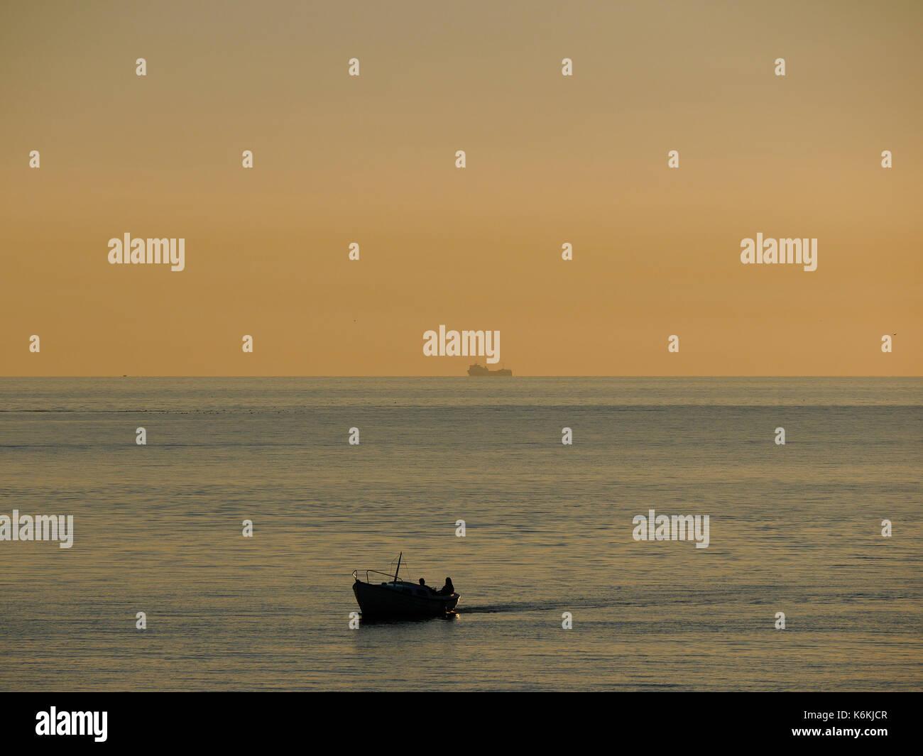 Coucher de soleil à Hönö, Klåva dans l'archipel de Göteborg. Bateau avec deux personnes en passant, navire de fret en arrière-plan. Banque D'Images