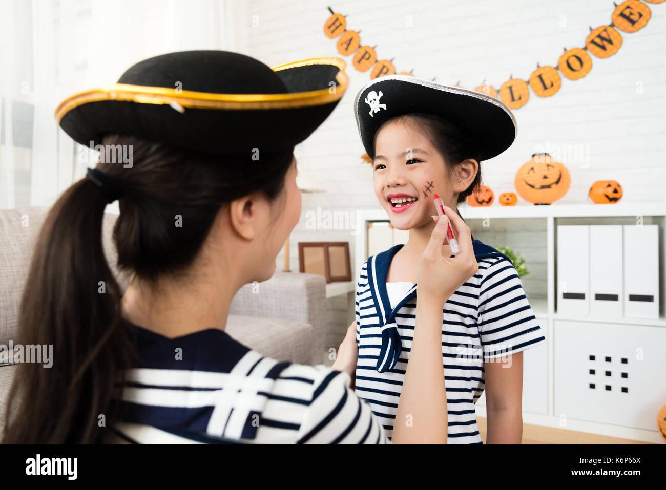 Pirate girl et mère jouer maquillage Halloween jeu et croquis des cicatrices  sur le visage à la maison