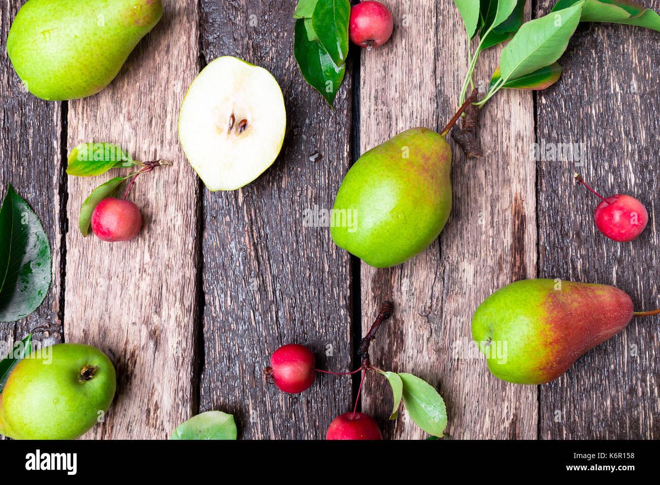 Poire et petite pomme sur fond rustique en bois. Vue de dessus du châssis. la récolte d'automne. Photo Stock