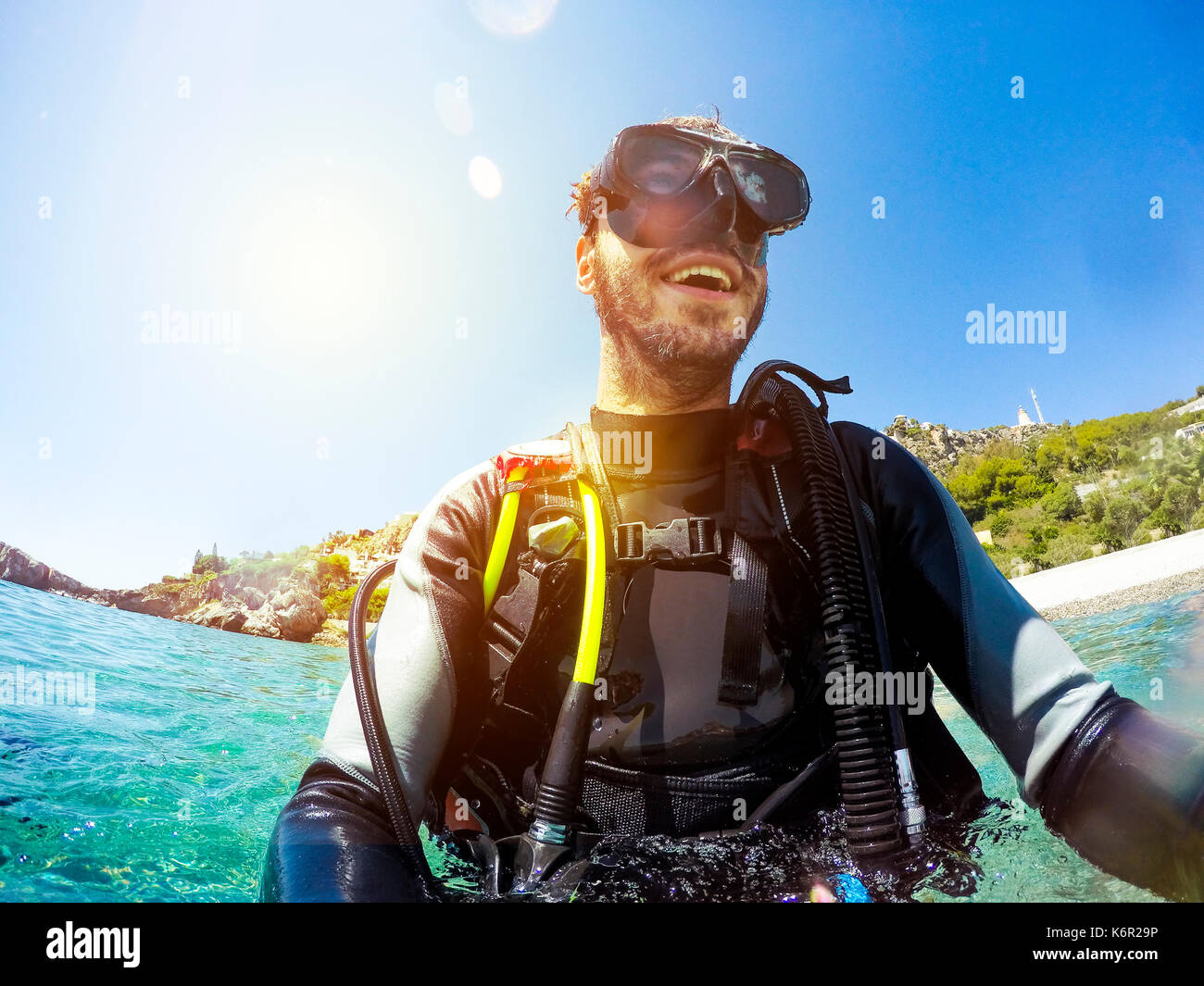 Smiling man en Plongée scaphandre flottant dans l'eau à la plage Photo Stock