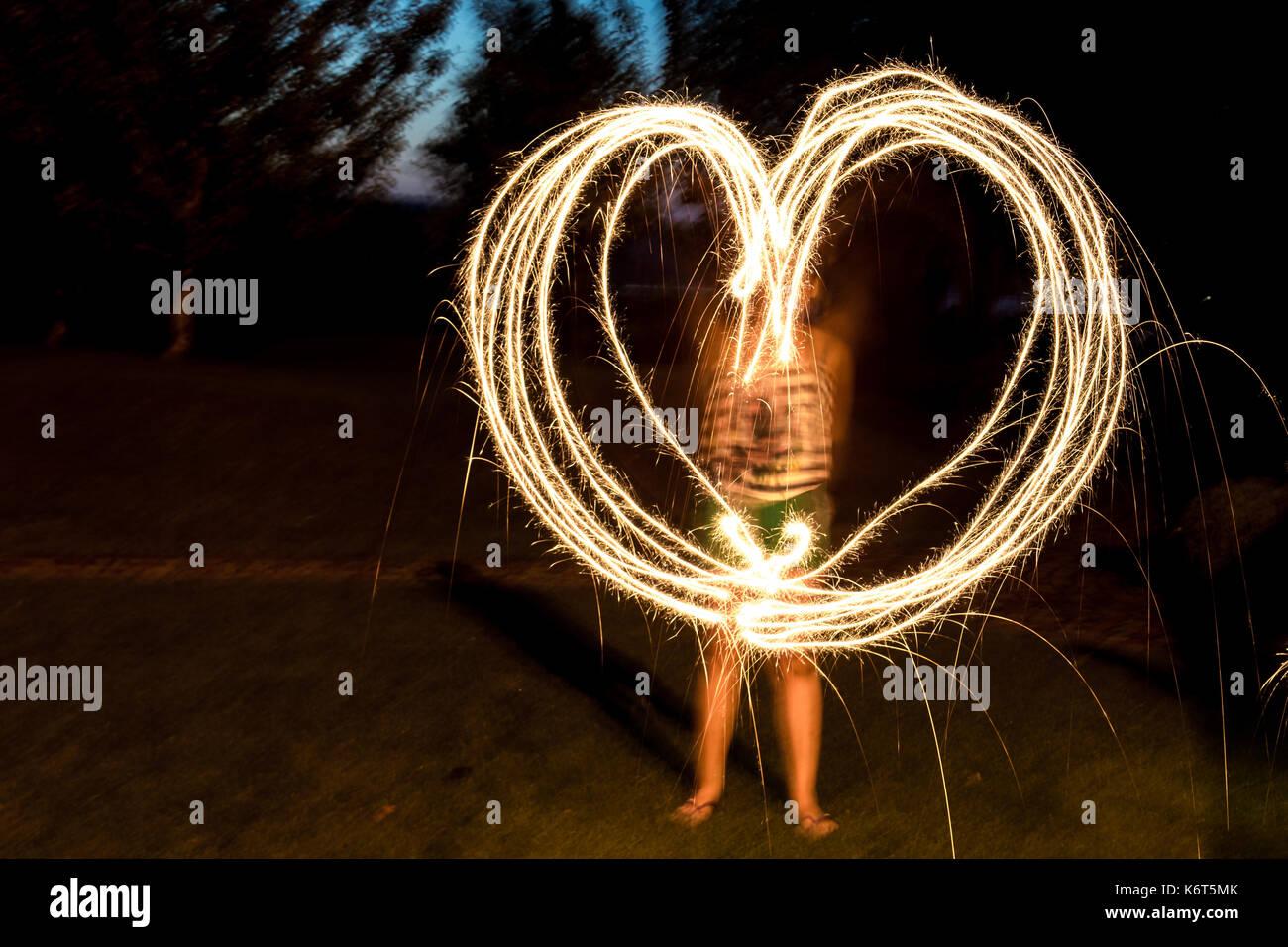 Une fille de coeur irrégulier avec feux de Bengale sparks. arrière-plan flou Banque D'Images