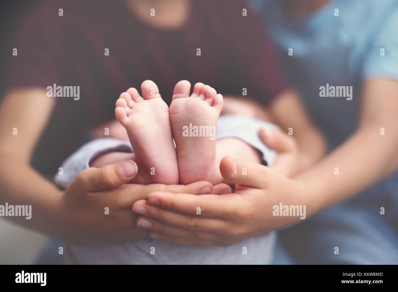 Petit bébé pieds dans les mains des frères, deux enfants tenant leur bébé dans les mains pieds frères Photo Stock
